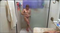 A loira fica excitada no banho e esfrega o chuveirinho no rabo