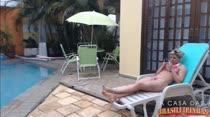 Mary relaxa na beira da piscina ouvindo música e usando o celular