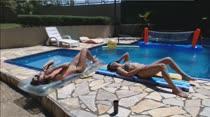 Gostosas tomam sol e conversam na beira da piscina